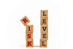 Risk level word written on cube shape. Risk level word written on cube shape wooden surface isolated on white background Royalty Free Stock Images