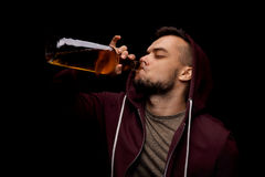 A risk man is drinking whiskey on a black background. A depressed guy dependent on alcohol. Copy space. stock images