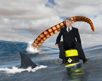Risk Management, Business, Sales, Marketing. A businessman floats on a radioactive nuclear waste barrel in the sea or ocean. A shark is attacking along with a stock image