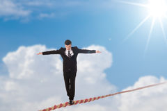 Risk management challenge. Businessman walking balance on rope over sky Royalty Free Stock Images