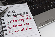 Risk Management. Concept on notepad and laptop stock photography