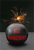 Risk management. Exploding bomb labeled risk management with burning fuse royalty free stock image