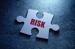 Risk management. Risk printed on a missing piece of jigsaw puzzle Stock Images