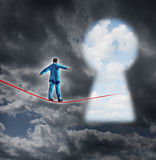 Risk And Opportunity. Business concept with a businessman on a dark storm background walking on a red tight rope that is leading into a key hole shaped as a Stock Photos