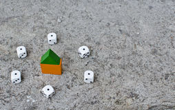 Risk Real Gamble. Risks of home mortgages, six dice with house in the middle. Housing market gamble concept Royalty Free Stock Photo