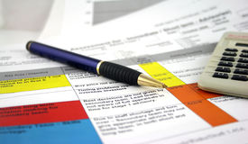 Risk Register. Risk analysis document with pen and a calculator, glasses put down to the side Royalty Free Stock Photography
