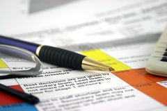 Risk Register 2. Risk analysis document with pen and a calculator, glasses put down to the side, shallow DOF Stock Images