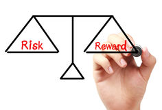Risk and reward balance. Hand with marker is drawing Risk and reward balance scale on the transparent white board Royalty Free Stock Photos