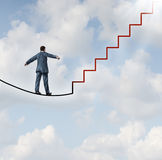 Risk Solutions. And adapting to change as a business idea with a businessman walking on a dangerous high wire tightrope that transforms into a red staircase Royalty Free Stock Photos
