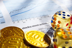 Risk on stock exchange. Two dices on stock data sheet with gold coins for a concept of risk on stock exchange royalty free stock images