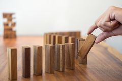 Risk and strategy in business, Close up of businessman hand gamb. Ling placing wooden block on a line of domino Stock Images