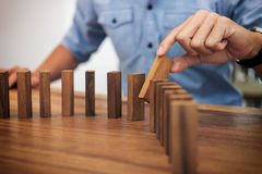Risk and strategy in business, Close up of businessman hand gamb. Ling placing wooden block on a line of domino Stock Photos