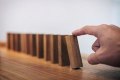 Risk and strategy in business, Close up of businessman hand gamb. Ling starting push wooden block on a line of domino Stock Photos