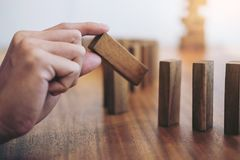 Risk and strategy in business, Close up of businessman hand gamb. Ling placing wooden block on a line of domino Royalty Free Stock Image