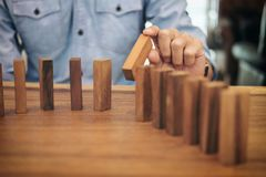 Risk and strategy in business, Close up of businessman hand gamb. Ling placing wooden block on a line of domino Stock Photo