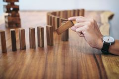 Risk and strategy in business, Close up of businessman hand gamb. Ling placing wooden block on a line of domino Royalty Free Stock Photos