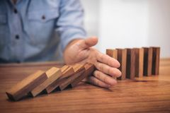 Risk and strategy in business, Close up of businessman hand stop. Ping wooden block from falling in the line of domino Royalty Free Stock Photos