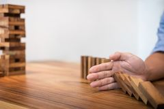 Risk and strategy in business, Close up of businessman hand stop. Ping wooden block from falling in the line of domino Stock Image