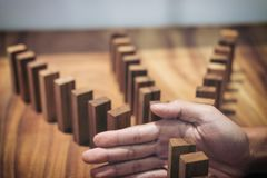 Risk and strategy in business, Close up of businessman hand stop. Ping wooden block between three way from falling in the line of domino Stock Images