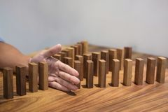 Risk and strategy in business, Close up of businessman hand stop. Ping wooden block between three way from falling in the line of domino Stock Image