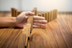 Risk and strategy in business, Close up of businessman hand stop. Ping wooden block between three way from falling in the line of domino Stock Photos