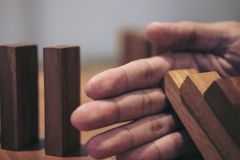 Risk and strategy in business, Close up of businessman hand stop. Ping wooden block between two way from falling in the line of domino Stock Photos