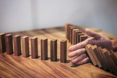 Risk and strategy in business, Close up of businessman hand stop. Ping wooden block between two way from falling in the line of domino Royalty Free Stock Photos