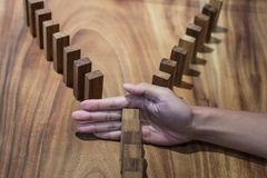 Risk and strategy in business, Close up of businessman hand stop. Ping wooden block between two way from falling in the line of domino Royalty Free Stock Photography
