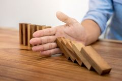 Risk and strategy in business, Close up of businessman hand stop. Ping wooden block from falling in the line of domino Royalty Free Stock Photography