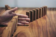 Risk and strategy in business, Close up of businessman hand stop. Ping wooden block between two way from falling in the line of domino Royalty Free Stock Photo
