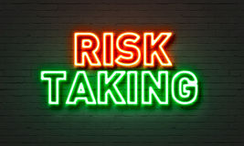 Risk taking neon sign on brick wall background. Risk taking neon sign on brick wall background Stock Photos