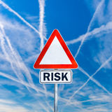 Risk. Triangular blank road sign with word Risk written in additional space below. Over blue sky with crossing contrails Royalty Free Stock Image