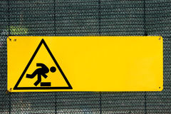 Risk of tripping road sign. Against a green net Royalty Free Stock Images