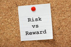 Risk VS Reward. The phrase Risk vs. Reward typed onto a piece of lined paper and pinned to a cork notice board Royalty Free Stock Image
