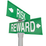 Risk Vs Reward Two 2 Way Road Street Signs ROI Investment. Risk and Reward on two green street or road signs to illustrate danger vs return on investment or ROI Royalty Free Stock Photos