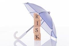 Risk wooden blocks under umbrella Stock Images