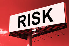 Risk word on billboard. Danger concept. Big billboard with RISK word on a red sky background royalty free stock image