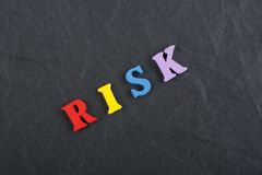 RISK word on black board background composed from colorful abc alphabet block wooden letters, copy space for ad text. Learning english concept royalty free stock photo