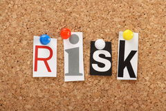 Risk. The word Risk in cut out magazine letters pinned to a cork notice board Stock Image