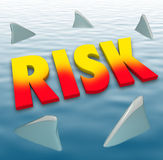 Risk Word Shark Fins Water Danger Deadly Warning Caution. Risk word in 3d letters on the water surface surrounded by shark fins to illustrate danger and Stock Photography