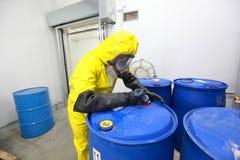 Riskabelt jobb - professionelln i enhetlig fyllning barrels med kemikalieer arkivfoton