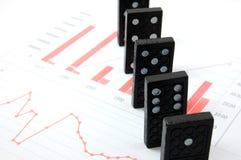 Riskanter Domino über einem Finanzgeschäftsdiagramm Stockfotos