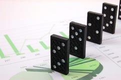 Riskanter Domino über einem Finanzgeschäftsdiagramm Lizenzfreie Stockfotos