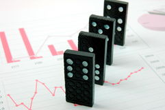 Riskanter Domino über einem Finanzgeschäftsdiagramm Lizenzfreies Stockfoto