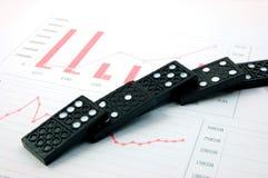 Riskanter Domino über einem Finanzgeschäftsdiagramm Stockbilder