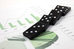 Riskanter Domino über einem Finanzgeschäftsdiagramm Stockbild
