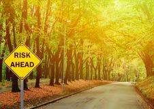 RISKERA FRAMÅT tecknet mot vägen i grön skog - affärsidé royaltyfria foton