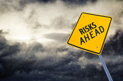 Risks Ahead Road Sign. Image of a yellow Risks Ahead road sign with a stormy weather clouds and rain. An open concept sign for business/ driving conditions royalty free stock photography
