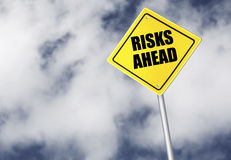 Risks ahead sign. Over cloudy sky Stock Image