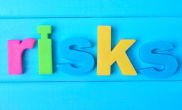 Risks word on table. Risks word on blue wooden table Royalty Free Stock Photos